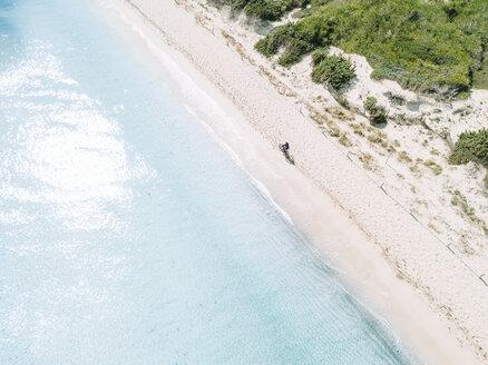 Aerial view of cyclists riding mountain bikes on white sandy beach, Mallorca, Balearic Islands, Spain - AURF07853