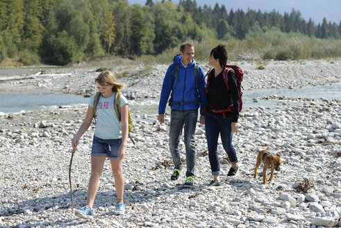 Family hiking with backpacks and a dog at the river Isar, Upper Bavaria, Germany - LBF02216