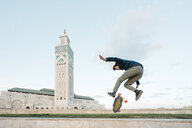 Side view of man skateboarding against Mosque Hassan II - CAVF54973
