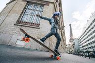 Full length of woman skateboarding against Eiffel Tower - CAVF54976