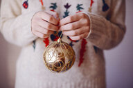 Midsection of woman holding bauble during Christmas at home - CAVF55003