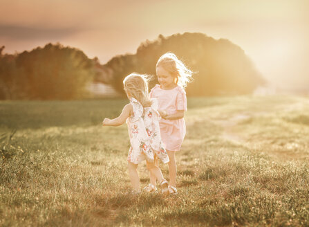 Sisters walking on grassy field against sky during sunset - CAVF55024