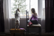 Full length of girl with dog sitting by window at home - CAVF55051