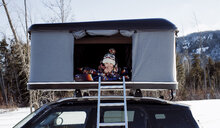 Portrait of smiling boy sitting in roof tent on car - CAVF55063