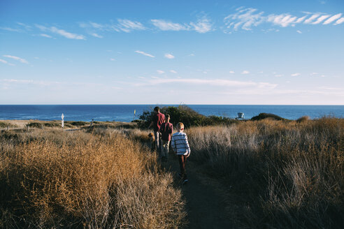 Rear view of father with dog and sons walking amidst plants on field by sea against sky - CAVF55075