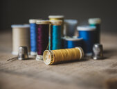 Close-up of colorful spools with thimbles on wooden table at workshop - CAVF55111