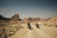 Rear view of friends riding motorbikes on dirt road against sky during sunny day - CAVF55123