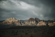 Scenic view of arid landscape against cloudy sky - CAVF55138