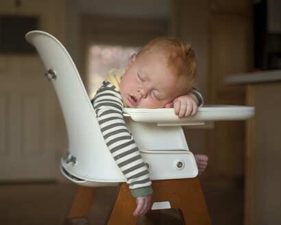 Cute baby boy sleeping on high chair at home - CAVF55147
