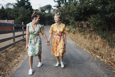 Happy female friends holding hands while walking on country road - CAVF55153