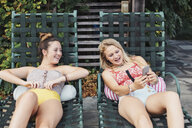 Teenage girl showing smart phone to friend while resting on lounge chair at poolside - CAVF55156