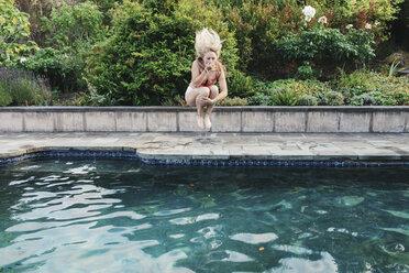 Carefree teenage girl jumping into swimming pool - CAVF55162