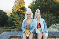 Portrait of female friends with hair wrapped in towel sitting on retaining wall - CAVF55165