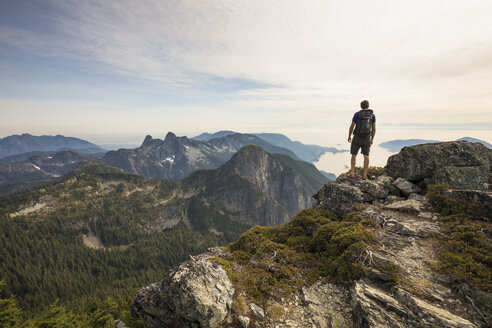 Rear view of carefree hiker with backpack standing on mountain against sky - CAVF55255