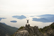 High angle view of hiker with arms raised standing on mountain against sky - CAVF55258
