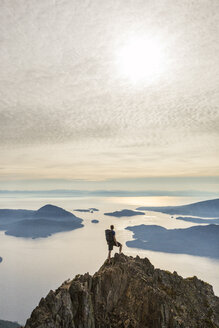 High angle view of carefree hiker with backpack standing on mountain against cloudy sky - CAVF55264