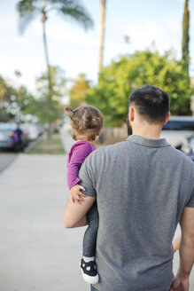 Rear view of father carrying daughter on footpath - CAVF55333