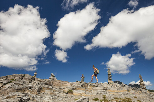 Low angle view of female hiker walking on rock formations against cloudy sky at North Cascades National Park - CAVF55438