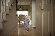 Portrait of cute baby boy drinking milk from bottle while standing on floor at home - CAVF55450