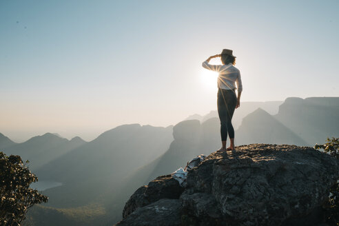 Rear view of woman looking at mountains while standing on rock during sunny day - CAVF55465