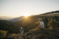 Side view of woman with backpack looking at view while sitting on mountain against sky during sunset - CAVF55468