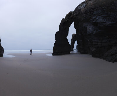 Mid distance view of man standing by rock arch at Cathedral Beach against sky - CAVF55471