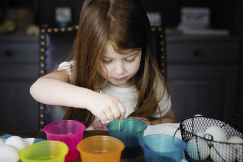 Cute girl coloring Easter Eggs on table at home - CAVF55483