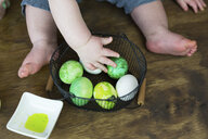 Midsection of baby boy playing with colored Easter Eggs in metallic basket on hardwood floor at home - CAVF55486