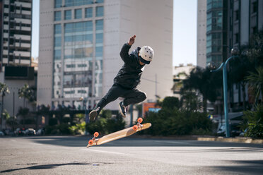 Man performing stunt while skateboarding on road in city - CAVF55492