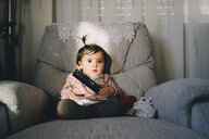 Cute baby girl with remote control sitting on armchair at home - CAVF55519