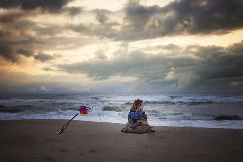 Girl looking at view while being wrapped in blanket on shore against stormy clouds - CAVF55540