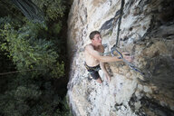 High angle view of shirtless hiker rock climbing - CAVF55543