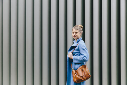 Side view portrait of confident young woman wearing trench coat while carrying purse against shutter in city - CAVF55552