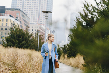 Cheerful young woman with purse wearing trench coat while holding disposable cup on boardwalk in city - CAVF55558
