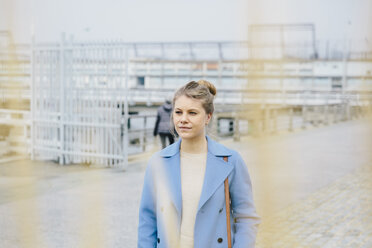 Thoughtful young woman wearing trench coat while standing in city - CAVF55561