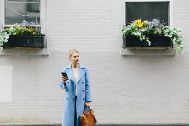 Young woman holding smart phone and purse while standing against building in city - CAVF55573
