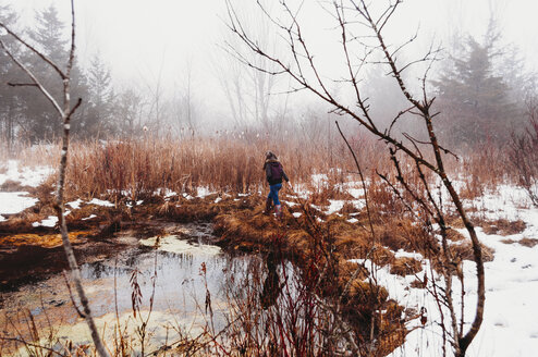 Rear view of girl walking on grassy field by lake in forest during winter - CAVF55585