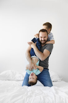 Cheerful father playing with sons on bed against wall at home - CAVF55618