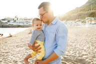 Loving father kissing cute daughter while carrying her at beach - CAVF55624