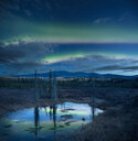 Scenic view of lake with reflection during aurora borealis against sky at night - CAVF55663