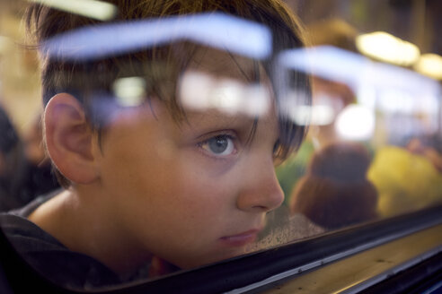 Boy looking through window while traveling in train seen through glass - CAVF55666