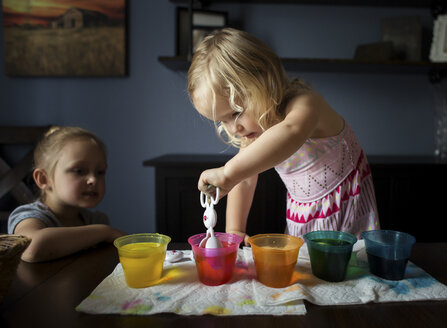 Girl looking at sister preparing Easter eggs on table at home - CAVF55687