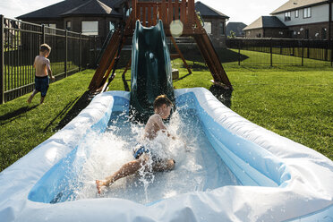 Brothers sliding into wading pool at park - CAVF55690