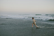 Side view of playful boy running on shore against sky at beach - CAVF55741