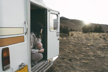 Woman looking away while crouching in camper van on field against clear sky - CAVF55756