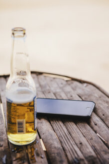 High angle view of mobile phone and beer bottle on table at beach - CAVF55771