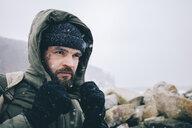 Man wearing warm clothing at beach during snowfall - CAVF55777