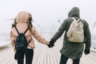 Rear view of couple with backpacks holding hands on pier against clear sky during winter - CAVF55780