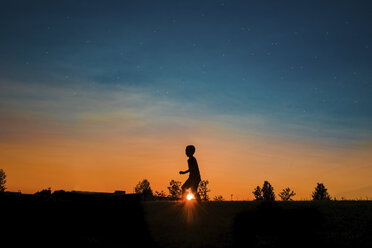 Silhouette boy walking on field against sky during sunset - CAVF55801