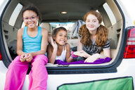 Cheerful friends playing in car trunk - CAVF55807